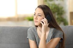 Ernste Frau, die an einem Telefonanruf teilnimmt Lizenzfreies Stockfoto