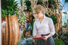 Ernste Frau, die im Blumenladen arbeitet stockbild