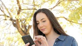 Ernste Frau, die intelligentes Telefon in einem Park verwendet