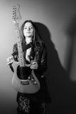 Ernste Frau, die mit E-Gitarre steht Stockfoto