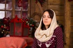 Ernste Frau, die nahe Weihnachtsdekorationen aufwirft stockbilder