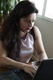 Ernste Frau, die zu Hause an ihrem Büro des Laptops arbeitet Lizenzfreie Stockfotografie