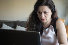 Ernste Frau, die zu Hause an ihrem Büro des Laptops arbeitet Stockfotos