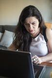 Ernste Frau, die zu Hause an ihrem Büro des Laptops arbeitet Stockbilder