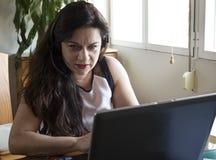Ernste Frau, die zu Hause an ihrem Büro des Laptops arbeitet Lizenzfreies Stockfoto
