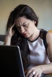 Ernste Frau, die zu Hause an ihrem Büro des Laptops arbeitet Lizenzfreies Stockbild