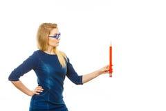 Ernste Frau hält großen Bleistift in der Hand Stockbild