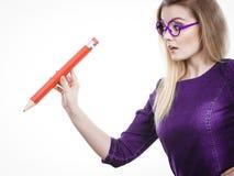 Ernste Frau hält großen Bleistift in der Hand Stockfotos