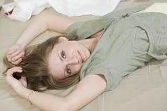 ernste Frau mit dem langen Haar, das auf Bett liegt Stockbilder