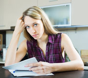 Ernste Frau mit Dokumenten in der Küche Stockbilder