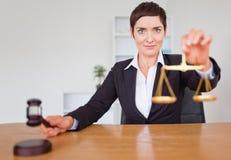 Ernste Frau mit einem Hammer und der Gerechtigkeitskala Lizenzfreies Stockbild
