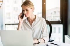 Ernste Frau verständigt sich durch Handy mit frustrieren Lizenzfreies Stockfoto