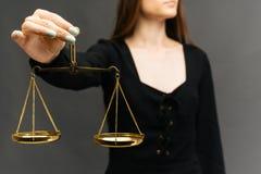 Ernste Frau, welche die Gerechtigkeitsskala auf dunklem Hintergrund hält stockbilder