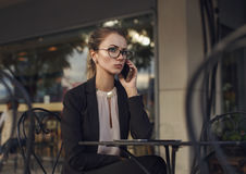 Ernste Geschäftsfrau in der Klage sprechend auf dem Mobiltelefon Stockbilder