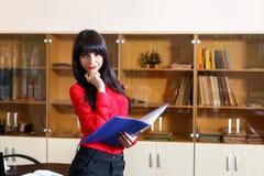 Ernste Geschäftsfrau in der roten Bluse mit einem Ordner von Dokumenten I Stockfoto