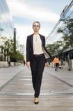 Ernste Geschäftsfrau, die an der Straße geht Stockbild