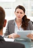 Ernste Geschäftsfrau, die einen Mann questionning ist Lizenzfreie Stockfotos