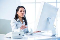 Ernste Geschäftsfrau, die Hand am Telefon hält stockfotografie