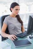 Ernste Geschäftsfrau, die an ihrem Computer arbeitet Stockbild
