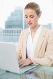 Ernste Geschäftsfrau, die an ihrem Laptop arbeitet Lizenzfreie Stockfotos