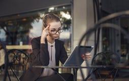 Ernste Geschäftsfrau, die mit der Tablette, denkend arbeitet Lizenzfreies Stockfoto