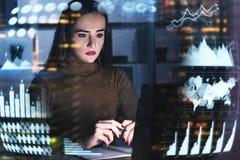 Ernste Geschäftsfrau im Büro, infographics Lizenzfreie Stockfotos