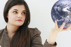 Ernste Geschäftsfrau mit der Welt in ihrer Hand Stockbild