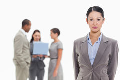 Ernste Geschäftsfrau mit Mitarbeitern im Hintergrund Lizenzfreie Stockbilder