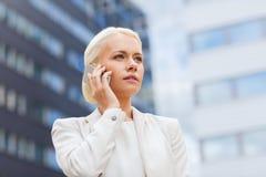 Ernste Geschäftsfrau mit Smartphone draußen Stockbild