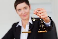 Ernste Geschäftsfrau, welche die Gerechtigkeitskala anhält lizenzfreie stockbilder