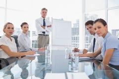 Ernste Geschäftsleute, die Kamera während einer Sitzung betrachten Lizenzfreie Stockfotos