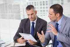 Ernste Geschäftsmänner, die Dokumente auf ihrer Tablette analysieren Stockbilder