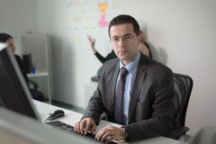 Ernste gewidmete Geschäftsmannarbeit im Büro auf Computer Wirkliche Wirtschaftswissenschaftlergeschäftsleute, nicht Modelle Banka