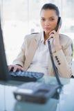 Ernste herrliche Geschäftsfrau, die das Telefon beantwortet Stockbilder