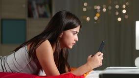 Ernste jugendlich schreibende Mitteilungen mit einem intelligenten Telefon auf einem Bett stock video