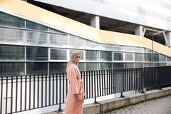 Ernste junge blonde Dame, die draußen geht Lizenzfreie Stockfotografie