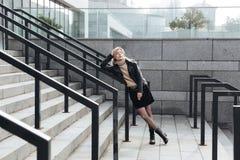 Ernste junge blonde Dame, die draußen Zigarette hält Lizenzfreie Stockfotos