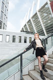 Ernste junge blonde Dame, die draußen Zigarette hält Lizenzfreies Stockbild
