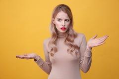Ernste junge blonde Dame mit den hellen Make-uplippen Stockfoto