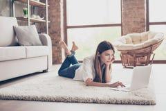 Ernste junge Dame ist das Studieren und liegt auf dem gemütlichen Teppich im livi Lizenzfreie Stockfotos