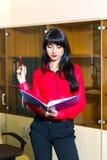 Ernste junge Frau in der roten Bluse mit einem Ordner von Dokumenten Lizenzfreies Stockbild