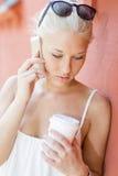 Ernste junge Frau, die draußen am Telefon spricht Lizenzfreies Stockbild