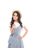 Ernste junge Frau im Strohhut zeigend auf Kamera Stockfotografie