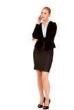 Ernste junge Geschäftsfrau, die durch das Telefon spricht lizenzfreies stockfoto