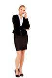 Ernste junge Geschäftsfrau, die durch das Telefon spricht stockfoto
