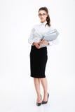 Ernste junge Geschäftsfrau, die Ordner steht und hält Lizenzfreie Stockfotos