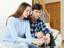 Ernste junge Paare mit Schwangerschaftstest Stockfotos
