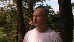 Ernste kahle Mitte alterte den Mann, der im Wald sideway schaut stock video
