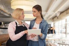 Ernste Kellnerin, die Arbeit mit ihrem Arbeitgeber bespricht Lizenzfreie Stockfotos