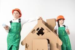 Ernste Kinder, die lernen, ein Haus zu bauen lizenzfreie stockfotografie